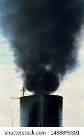 Thick black smoke from ship's funnel close up. Pollution by ship's engine.