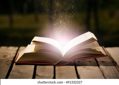 Thick book lying open on wooden surface, magic star dust coming out of it, beautiful night light setting, magician concept shoot