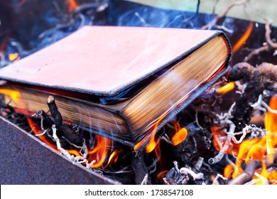 A thick book on fire. Burning books. Destruction of banned books