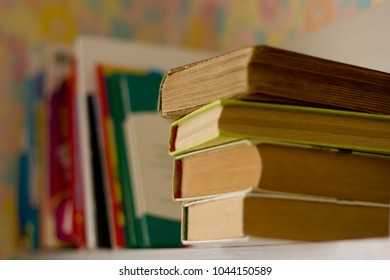 thick books on a wooden shelf