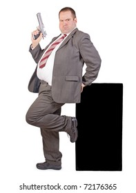 Thick businessman with a gun standing near empty blackboard. Overweight man in a suit holding a pistol at the billboard, isolated on white background. Fat agent on the Guard is armed with a firearm.