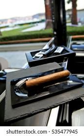 Thick cigar and supplies. Cigar cutter and cuban cigar set.