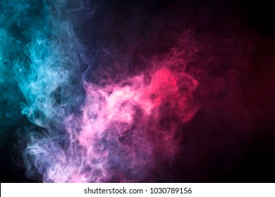 Thick colorful smoke of blue, pink, red on a black isolated background. Background from the smoke of vape