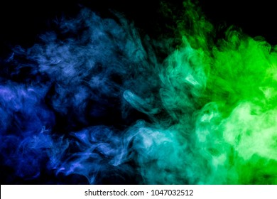 Thick colorful smoke of green and blue on a black  isolated background. Background from the smoke of vape