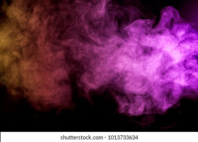 Thick colorful smoke of  purle and pink on a black isolated background. Background from the smoke of vape