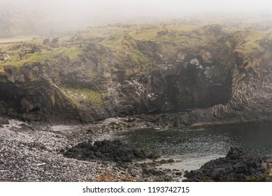 Thick fog conditions at Badstofa Rock Foamation in Hellnar, Iceland