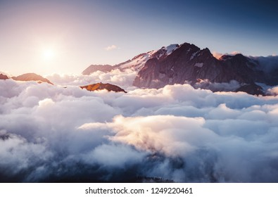 Thick fog covered the ridge in morning. Location place Val di Fassa valley. Scenic image of famous glacier Marmolada, passo Sella, Dolomiti, South Tyrol, Italy, Europe. Explore the beauty of world.