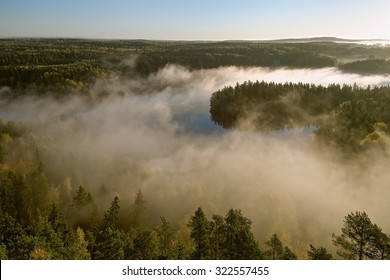 Thick fog covering the forest and the lake in early morning landscape. Peaceful view from the Aulanko lookout tower in Finland.
