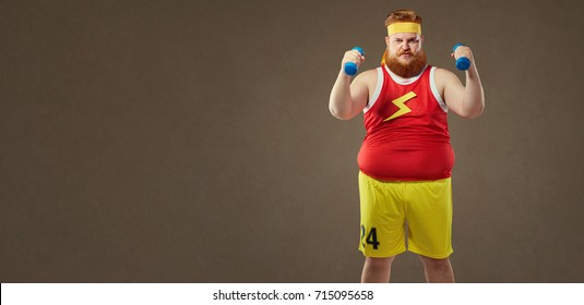 Thick funny guy in sportswear with small dumbbells