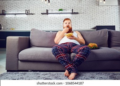 Thick funny man in pajamas eating a burger sitting on the couch.