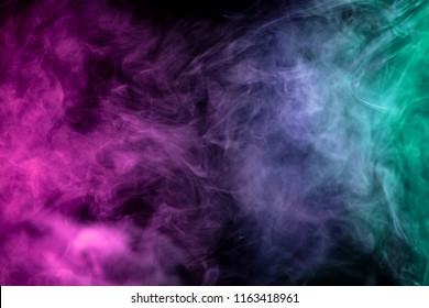 Thick green, pink and white smoke on a black isolated background. Background from the smoke of vape