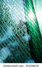 thick green plastic safety net for construction site, note shallow depth of field