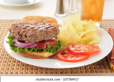 a thick hamburger with potato chips
