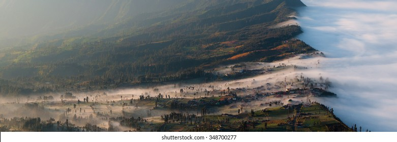 Thick haze, white mist and Fog sliding in a field by the mountains of volcano Bromo