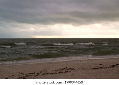 Thick heavy storm clouds fill the sky over the gulf of Mexico in bonita springs, Florida, as waves crash on bonita beach.