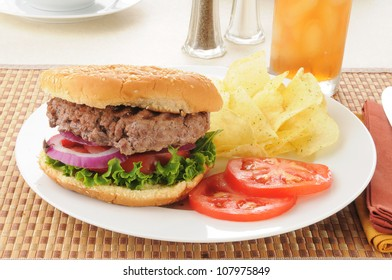 A thick homemade hamburger with potato chips