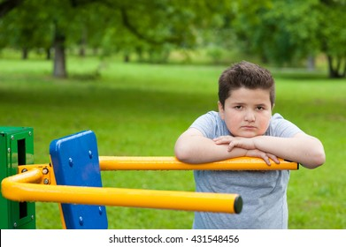 thick kid next to a training machine in the park