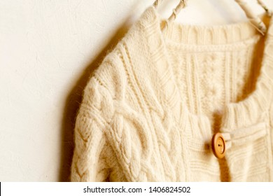 fc135aa49ebce8 a thick knitted cardigan in white hanging on clothes hanger on white  background. Close up