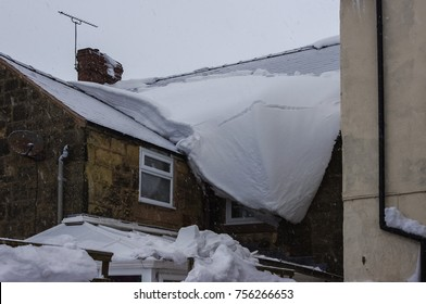 Thick layer of snow hanging off roof covering window during a blizzard. Large crack showing where the icy snow eventually will break and fall off.