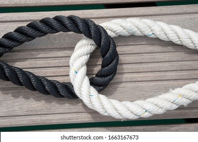 Thick loops of black and white nautical rope embracing outdoors on a wooden background