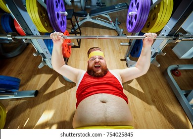 Thick man doing exercises with a barbell in the gym.