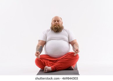 Thick man is meditating with relaxation. He is sitting in lotus position. His eyes are closed with serenity. Isolated