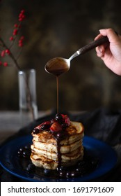 Thick maple syrup is poured over a heaping stack of pancakes covered in blueberries, strawberries and syrup