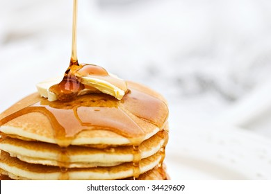 Thick maple syrup pouring onto a stack of fresh pancakes. Selective focus on butter with blurred background.