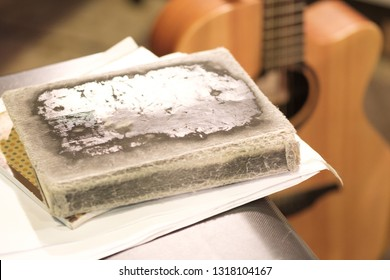 thick old book with battered crusts in the foreground, blurred guitar background on stage