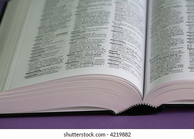 The thick open book lays on a purple background