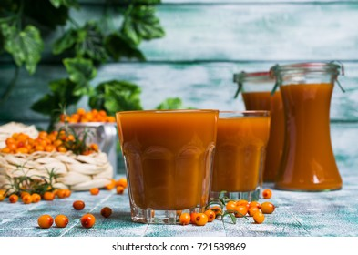 Thick orange drink in the glass on a wooden background with sea buckthorn berries. Selective focus.