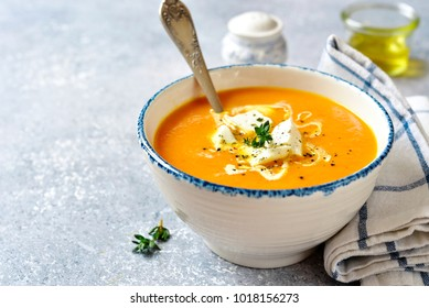 Thick pumpkin soup with feta cheese and thyme in a vintage bowl on a light slate, stone or concrete background.