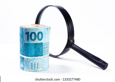 Thick roll of Brazilian Real banknotes in front of a magnifying glass lit from behind with the one hundred value facing forward. Clean studio shot currency with magnify tool against a white background