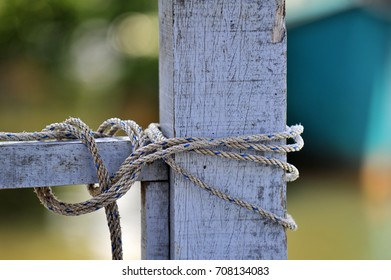 Thick ropes wrapped around a mooring post, selective focus