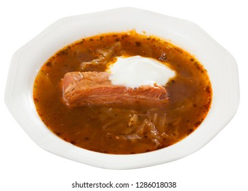 Thick Russian-style cabbage soup (Shchi) with pork cooked in mushroom broth served with sour cream. Isolated over white background