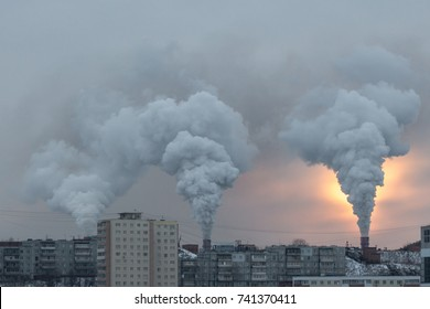 Thick smoke puffs from the pipes of the factory, the rays of the sun through the smoke