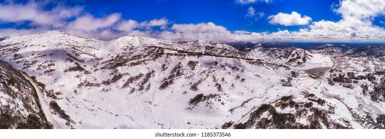 Thick snow cover around Perisher valley ski resort town in Snowy mountains of Australia during winter skiing season with lots of chair lifts and tracks down from tall peak of Mt Perisher.