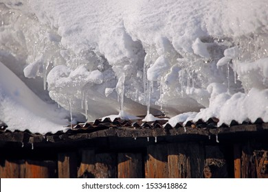 Thick snow on the wooden roof. It melts under sunlight and forms a transparent icicle. Cold winter outdoor buildings scene.