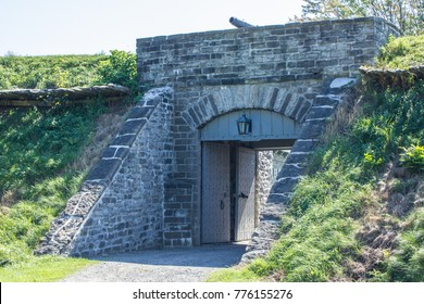 The thick stone walls and open wooden doors of Fort Wellington wait for visitors in a park in historic Prescott, Ontario, Canada.