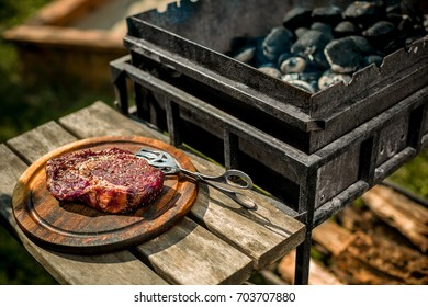 A thick strip steak being grilled outdoors
