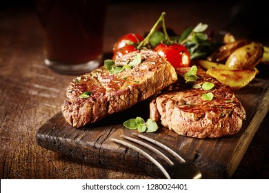 Thick tender roasted or grilled beef fillet medallions served on an old vintage wooden board with tomatoes and potato wedges