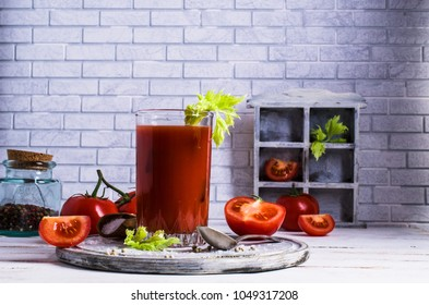 Thick tomato juice with celery and spices in a glass on the table. Selective focus.