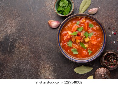 Thick tomato soup with meat, cereals and vegetables. Traditional Oriental cuisine, spicy stew with beef or lamb, rice and spices. Food on dark background