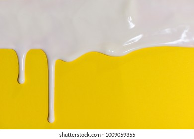 Thick white paint dripping down the yellow wall.