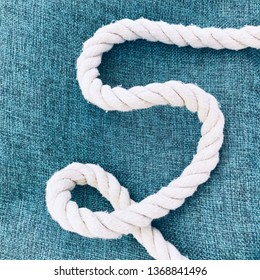 thick white rope-rope on a rough linen fabric of blue. Marine background.