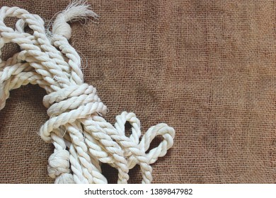 A thick white twisted rope lies on coarse burlap