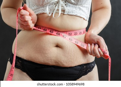 thick woman check her stomach fat with tape