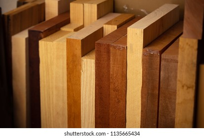 Thick wooden planks resting on a shelf. Mahogany, Alder, Ash, Bassswood, wood body planks used for electric guitar building.