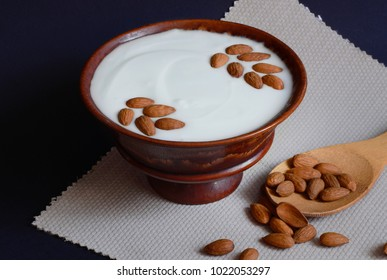 Thick yogurt with almonds in a clay plate. Tasty and healthy food