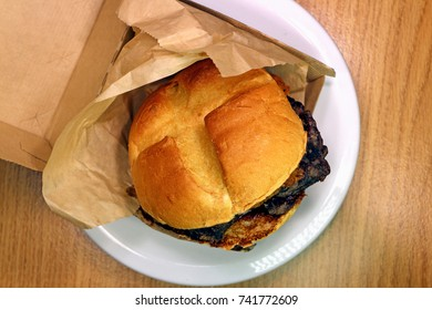 Thick-cut venison, topped with crispy onions, and juniper berry sauce. Venison steak  venison sandwich, in wrapper and serving box. Overhead view, limited-edition Arby's venison sandwich